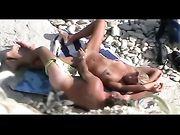 Pareja desnuda pillada teniendo sexo en la playa