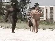 Mujer desnuda con un hombre negro desnudo rodó en la playa