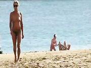 Una mujer madura en topless en la playa
