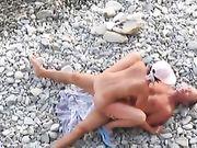 Una pareja nudista hace sexo en la playa y un voyeurista está filmando